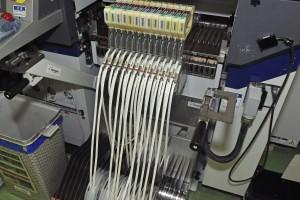 高速機。テープみたいなものにコンデンサーが貼り付けられていて、これを基盤にとりつけます。